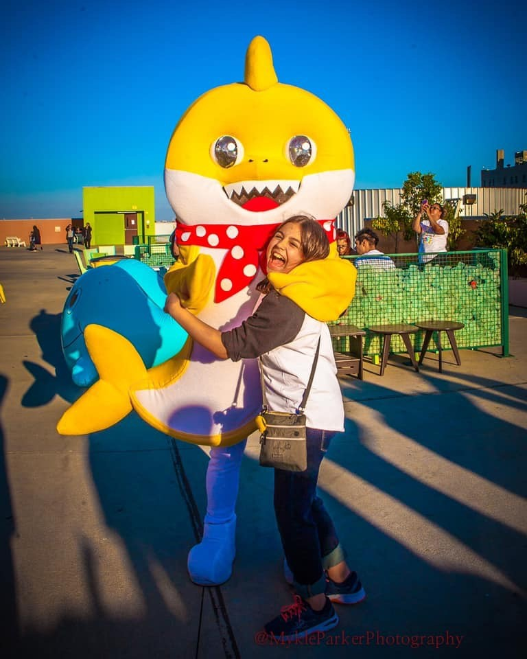 Baby Shark hugging a girl who is smiling and happy